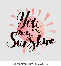 """Lettering """"You are my sunshine."""" Uppercase letters, hand-drawing. Dark letters on a pink watercolor sun"""