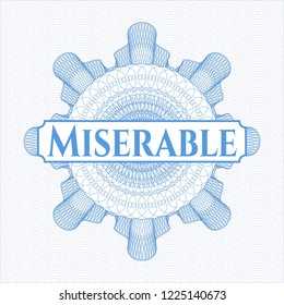 Light blue money style emblem or rosette with text Miserable inside