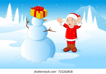 Little boy dressed in Santa Claus playing with snowman with winter background
