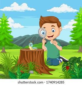 Little boy looking at caterpillar using magnifier in the garden
