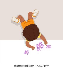 Little boy lying on his stomach and painting butterfly with his hands, top view of child on the floor