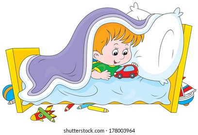 Little boy playing with a toy car under a blanket in his bed
