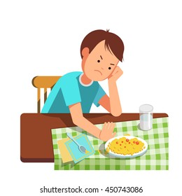A little boy refusing food, kid does not want to eat. Kid sits at the table and does not want to eating