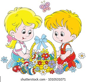 Little children with a decorated Easter basket of colorfully painted eggs and flowers