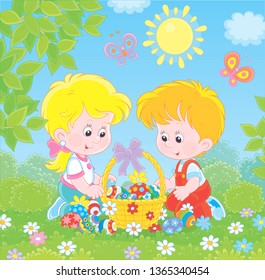 Little children with a decorated Easter basket of colorfully painted eggs among flowers on green grass of a lawn on a sunny spring day, vector illustration in a cartoon style
