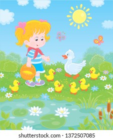 Little girl feeding a white duck and small yellow ducklings among flowers by a pond with water-lilies on a sunny summer day, vector illustration in a cartoon style