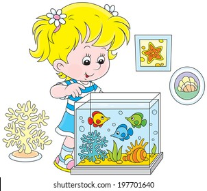 Little girl watching colorful tropical fishes in an aquarium