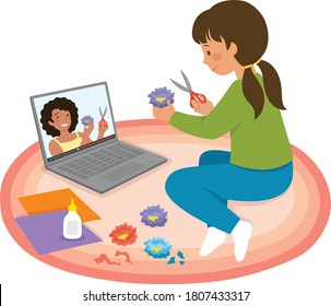 Little girl watching craft tutorial video on a laptop and making paper flowers