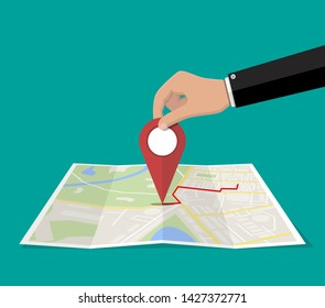 Location pin in hand and paper map. City map with houses, parks, streets and roads. City aerial view. GPS, navigation and cartography. Vector illustration in flat style
