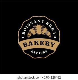 Logo badge of croissant bread in vintage design. bakery label design on black background