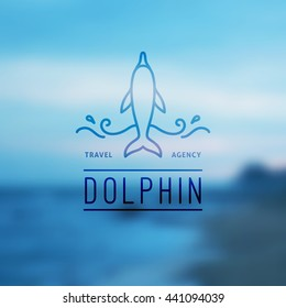 logo of dolphin and waves on blurred background of seascape, vector template for travel agency