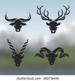 Logos horned animals. On blurred background.Buffalo, deer, mountain goat,  sheep.