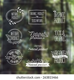 Logotypes set. Badges, labels, ribbons, plants elements, wreaths and laurels, branches. Organic, bio, ecology, eco natural design template. Hand drawing. Vintage vector on blurred background forest
