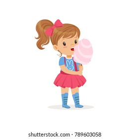 Lovely toddler kid eating sweet cotton candy on stick. Brown-haired girl with ponytail in blue t-shirt with bunny print and pink skirt with suspenders. Flat vector design