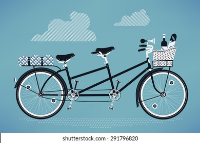 Lovely vintage old fashioned tandem bike with front and rear racks, picnic basket with bottle of wine and baguette bread and folded picnic plaid