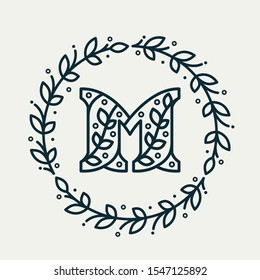 M letter logo consisting of floral pattern in a circle laurel wreath. Linear heraldic vector font. Can be used for boutique, cafe, restaurant, royalty, hotel, jewelry or sport industry.