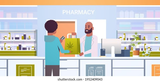 male doctor pharmacist giving medical cannabis package to african american client at pharmacy counter modern drugstore interior medicine healthcare concept horizontal portrait