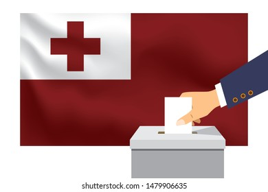 Male hand puts down a white sheet of paper with a mark as a symbol of a ballot paper against the background of the Tonga flag. Tonga the symbol of elections.