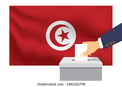 Male hand puts down a white sheet of paper with a mark as a symbol of a ballot paper against the background of the Tunisia flag. Tunisia the symbol of elections.