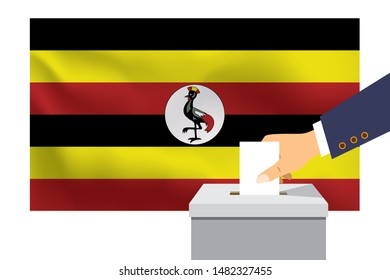 Male hand puts down a white sheet of paper with a mark as a symbol of a ballot paper against the background of the Uganda flag. Uganda the symbol of elections.