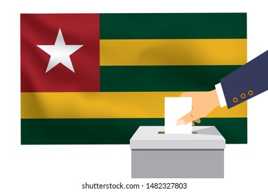 Male hand puts down a white sheet of paper with a mark as a symbol of a ballot paper against the background of the Togo flag. Togo the symbol of elections.