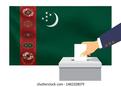 Male hand puts down a white sheet of paper with a mark as a symbol of a ballot paper against the background of the Turkmenistan flag. Turkmenistan the symbol of elections.