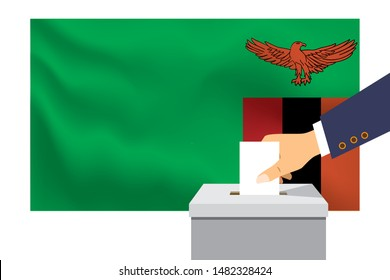 Male hand puts down a white sheet of paper with a mark as a symbol of a ballot paper against the background of the Zambia flag. Zambia the symbol of elections.