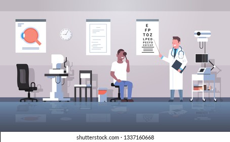male ophthalmologist checking african american man patient eyesight doctor in uniform pointing letters at eye chart medicine and healthcare concept oculists office interior horizontal