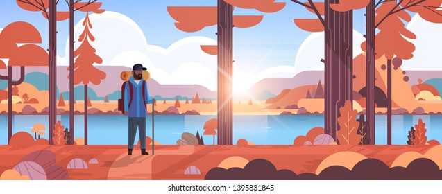 male tourist hiker with backpack african american man traveler holding stick standing in forest hiking concept autumn landscape nature river mountains background horizontal full length