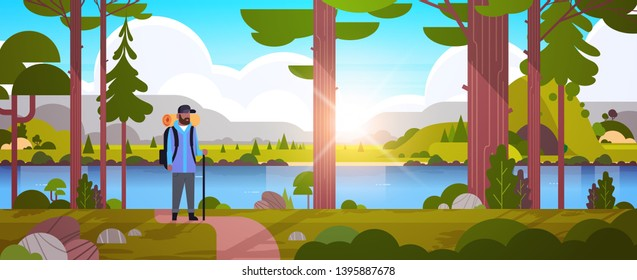 male tourist hiker with backpack african american man traveler holding stick standing in forest hiking concept sunrise landscape nature river mountains background horizontal full length