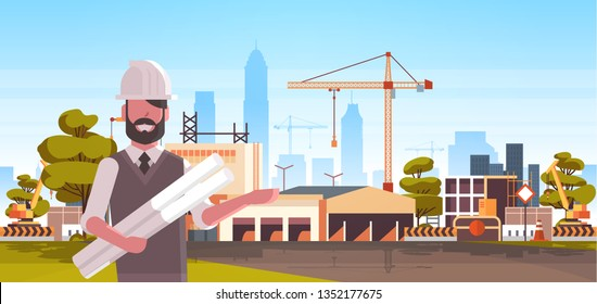 man architect in helmet holding rolled up blueprints over city construction site tower cranes building residential buildings cityscape skyline background portrait horizontal
