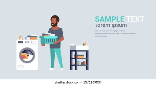 man with clothes basket standing near washing machine african american guy doing housework laundry room male cartoon character full length flat horizontal copy space
