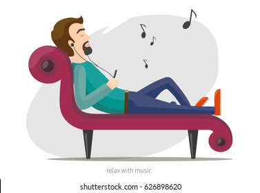 Man lies on the sofa and listening music in headphones