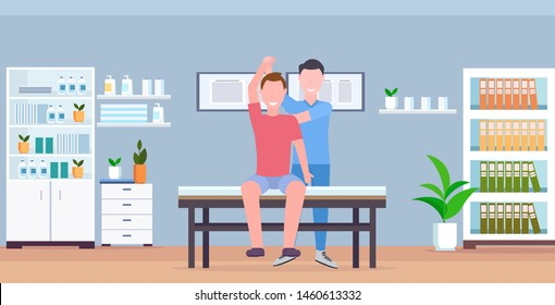 man patient sitting on table masseur therapist doing healing treatment massaging patient body manual sport physical therapy concept modern clinic hospital room interior horizontal