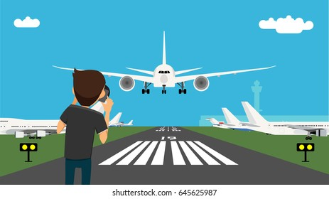 Man taking picture of the glide path and landing plane using professional camera. Aircraft spotting concept