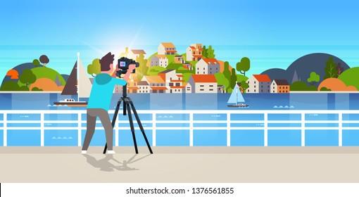 man travel photographer taking nature picture of mountain city island guy using dslr camera on tripod landscape background horizontal
