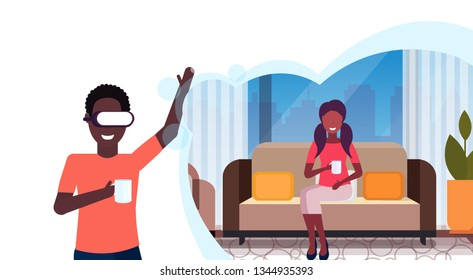 man wearing digital glasses virtual reality african american, woman sitting couch drinking tea or coffee