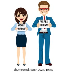 Man and woman business people holding white board with we are hiring text standing