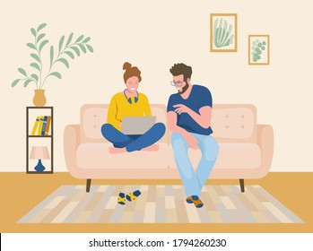 A man and a woman are sitting on the sofa and looking at the laptop screen. Freelance or studying concept. Young family