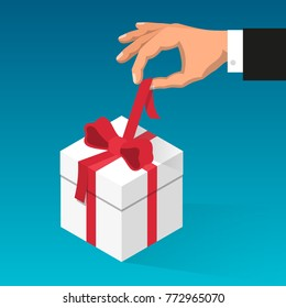 Man's hand unties red ribbon on the box with gift.