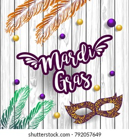 Mardi Gras abstract with ribbons, mask, feather  and banner on the wooden background. Eps 10 vector file.