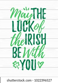 May The Luck Of The Irish Be With You handdrawn dry brush style lettering on white wooden background, 17 March St. Patrick's Day celebration. Suitable for greeting card design, poster, etc., vector
