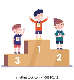 Medalists kids standing on competition winner podium with first, second and third place medals.