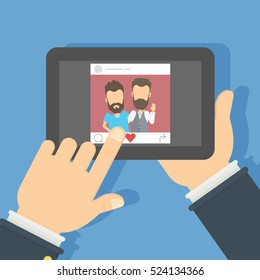 Men on the screen. Hand holding tablet with photo of the male frends. Concept of applications or social networks. Like button.