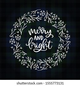 Merry and bright hand lettering. Christmas greeting card, invitation. Wreath of snowflakes, ornamental  branches, white text over tartan, green checkered plaid. Winter vector calligraphy illustration.