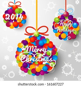 Merry Christmas 2014 handwritten swirl lettering on greeting card made from bundle of bright confetti on paper with snowflakes, in shapes of christmas balls. With place for your text