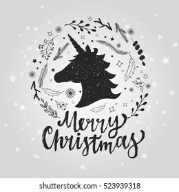 Merry christmas lettering with snowflakes, flowers and unicorn. Hand drawn festive card for your design. xmas unicorn design on shiny background.