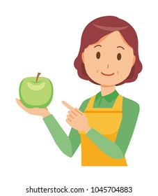 A middle-aged housewife wearing an apron has a green apple