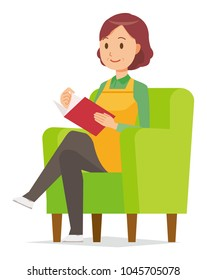 A middle-aged housewife wearing an apron is reading on a sofa