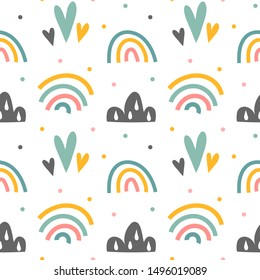 Minimalistic scandinavian style baby seamless background. Hand drawn rainbow and clouds in pastel colors. Simple doodle elements for baby room, good as wallpaper, textile fabric or wrapping paper.